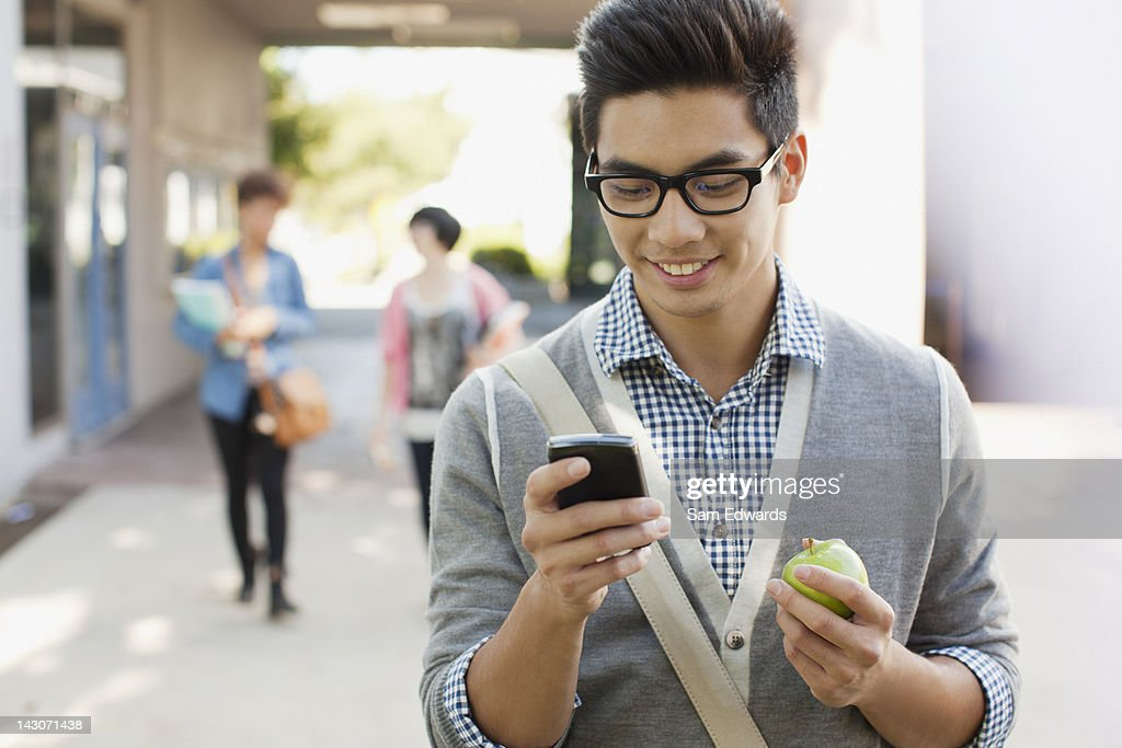 Student using cell phone outdoors : Stock Photo