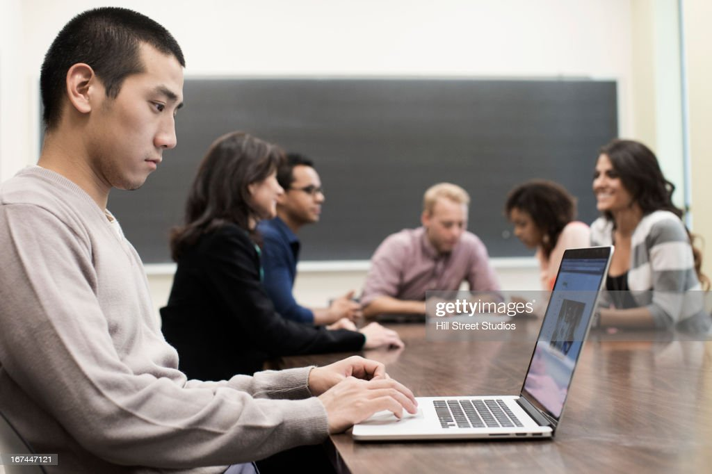 Student using laptop in classroom : Stock Photo