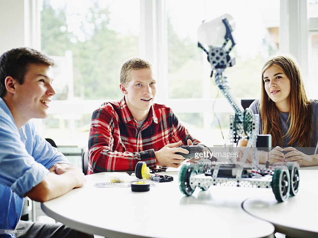 Student sitting at table in high school classroom with classmates using remote control to operate robot