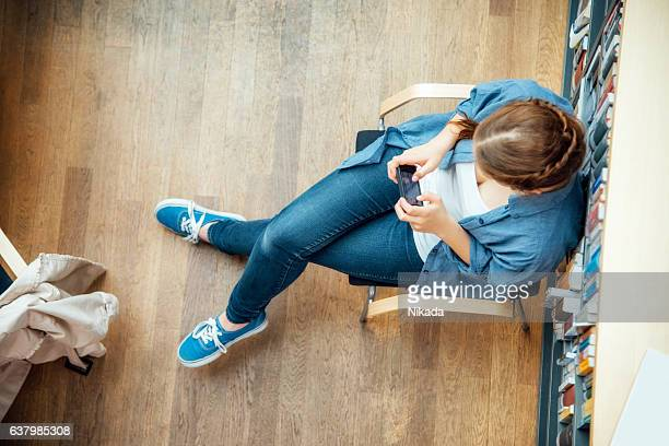 student using smart phone while sitting against bookshelf in classroom
