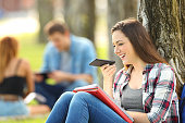 Student using voice recognition with a smart phone to record notes sitting on the grass in a park