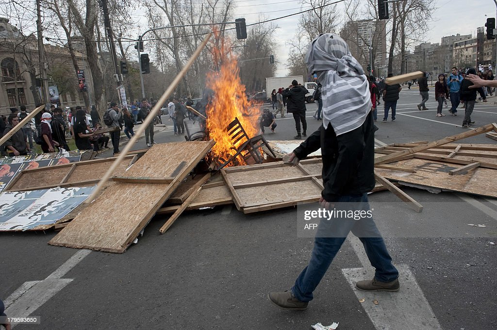 A student walks near a bonfire during clashes with riot police in a protest to demand Chilean President Sebastian Pinera's government an intensive educational reform and to break with other legacies of the dictatorship of Augusto Pinochet (1973-1990), in Santiago, on September 5, 2013. AFP PHOTO/Claudio SANTANA