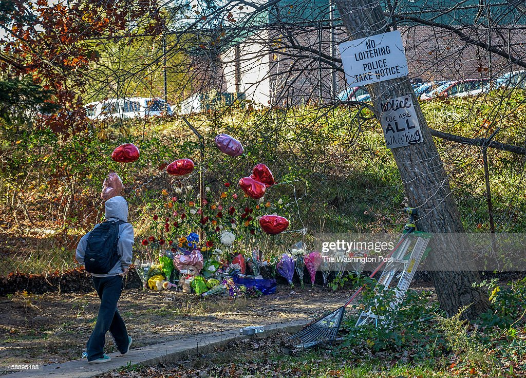 A student walks past a growing memorial at the site of the shooting death of teenager Brenden Wilson on November 2014 in Woodbridge VA