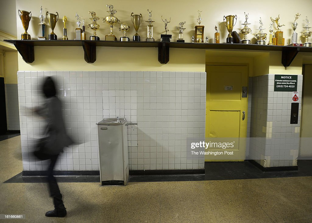 A student walks past a portion of old trophies that are still on display in the main hallway at Spingarn High School in Washington DC, February 12, 2012 .