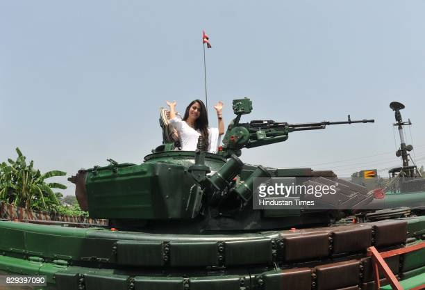 A student waving to her friends from top of an army tank during an exhibition at Jammu University on August 10 2017 in Jammu India