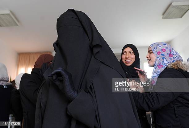 A student wearing a niqab uses a telephone on November 29 2011 in the building housing the office of the dean of the Faculty of Arts at the...