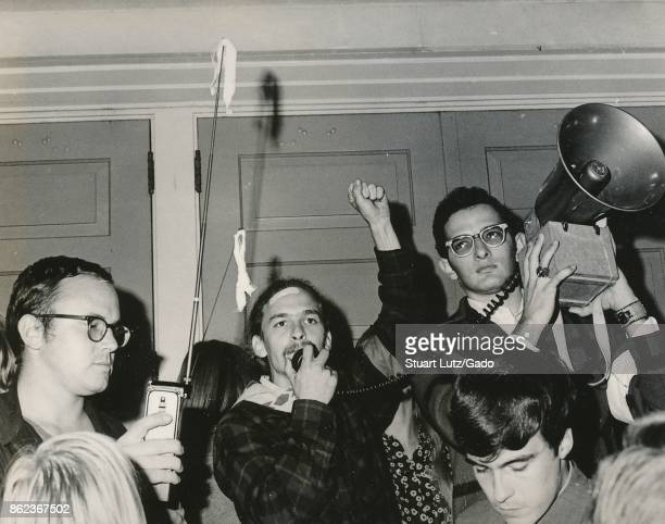 Student wearing hippie attire holding his fist into the air and speaking into the microphone of a bullhorn loudspeaker during an anti Vietnam War...