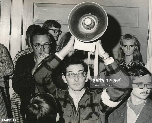 A student wearing hippie attire holds a bullhorn loudspeaker above his head while another student speaks into the microphone during an anti Vietnam...