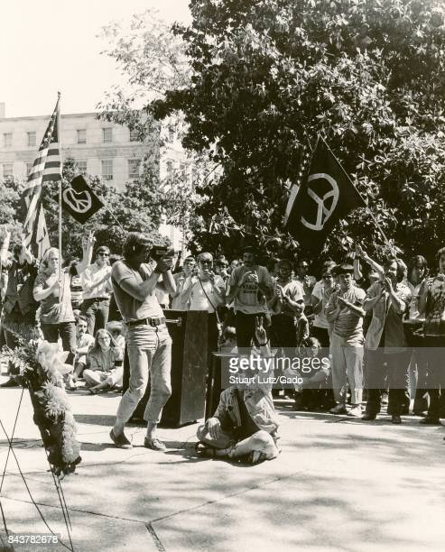 A student wearing hippie attire sits in the middle of a quad and makes a peace hand symbol with a raised hand during a sit in student protest against...