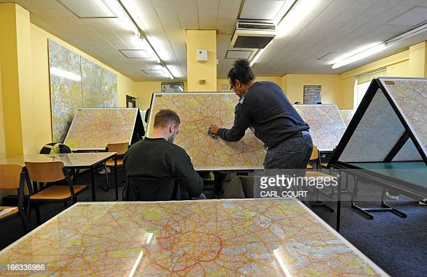 A student wipes a map of London clean in a test centre in north London on February 28 2013 All London Black Cab drivers are required to pass the...
