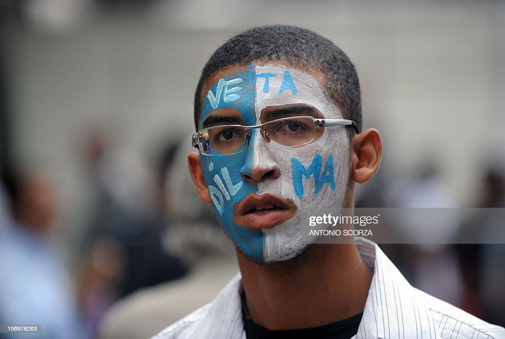 A student with painted face takes part in a demonstration demanding Brazilian President Dilma Roussef to veto a bill that would redistribute oil royalties in favor of non-oil producing states, in Rio de Janeiro, Brazil, on November 26, 2012. Both Rio de Janeiro's mayor Eduardo Paes and governor Sergio Cabral warned that the new oil royalties share-out plan will jeopardize the financing of the 2014 World Cup and the 2016 summer Olympics. AFP PHOTO ANTONIO