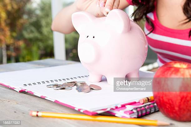 Student with piggy bank, notebooks and apple