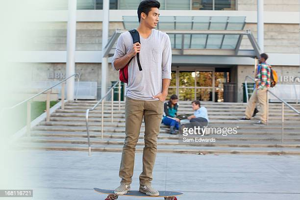 Student with skateboard on campus