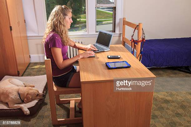 Student with visual impairment using her talking computer in her dorm room with her service dog