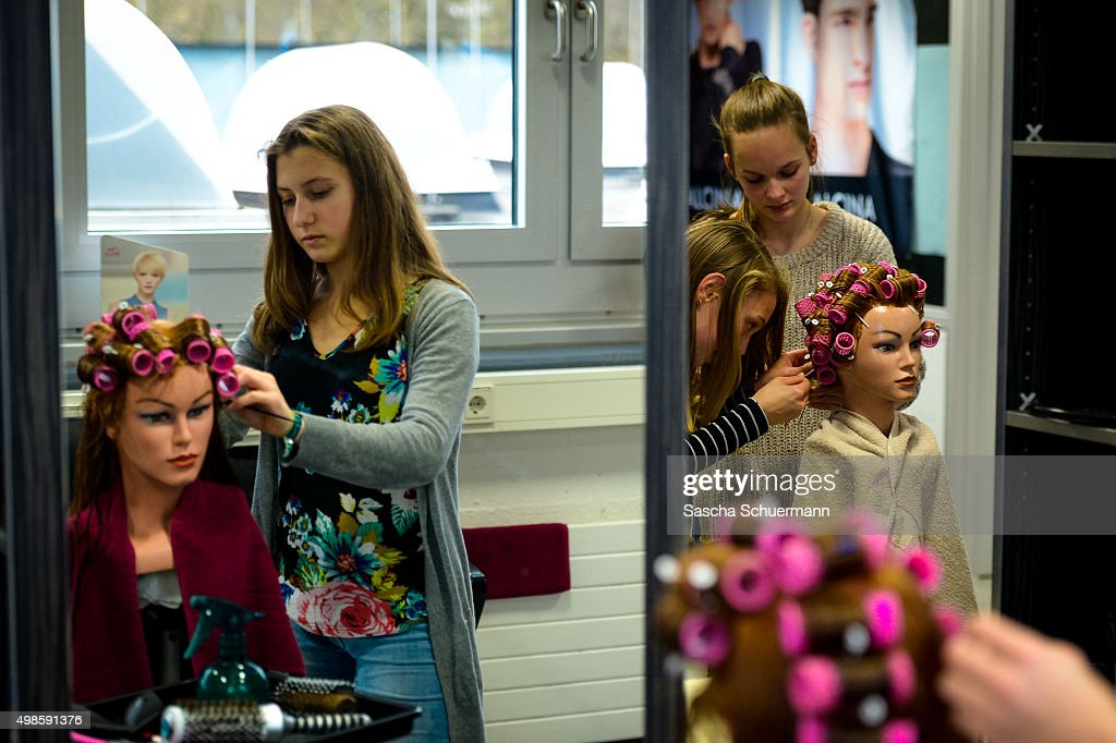 A Student working as a hairdresser with a dummy at the Vocational training center of the Chamber of Crafts (Bildungszentrum Butzweilerhof der Handwerkskammer) on November 24, 2015 in Cologne, Germany. German industry has complained in recent years of being unable to fill tens of thousands of trainee positions and some see the influx of nearly a million migrants this year as a possible opportunity to narrow the gap.