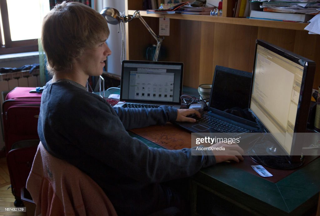 Student working at desk in room : Stock Photo