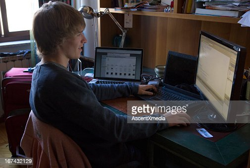 Student working at desk in room : Foto de stock