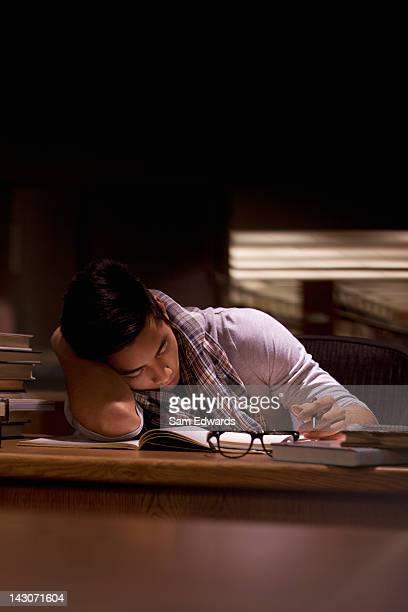 Étudiant travaillant dans une bibliothèque de nuit
