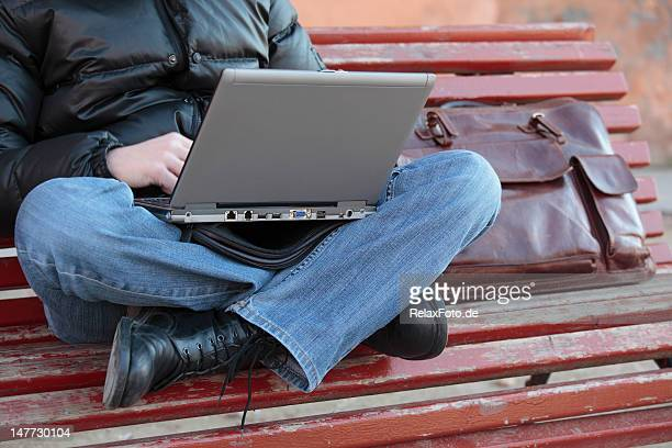 Student working with laptop sitting cross-legged on bench (XXXL)