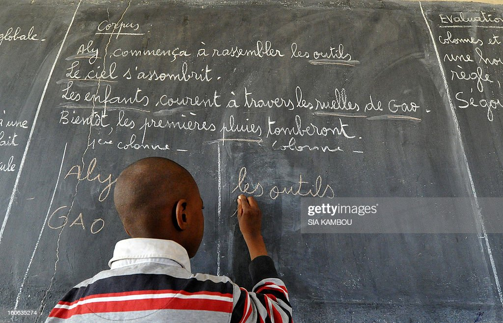A student writes at the blackboard in a classroom in Gao, in the north of Mali, on the first day of the reopening of schools after the French bombing of Islamist targets, on February 4, 2013. Schools reopened today in Gao after the town was taken on January 26 by French and Malian forces from Islamists who had been occupying it for the last year.