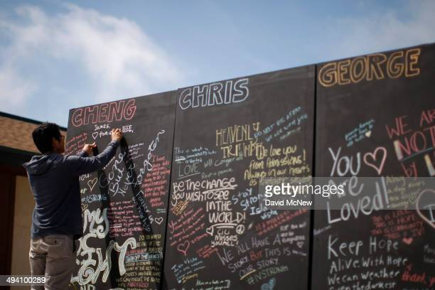 A student writes chalk messages on a memorial wall for slain students on the Day of Mourning and Reflection for the victims of a killing spree at...