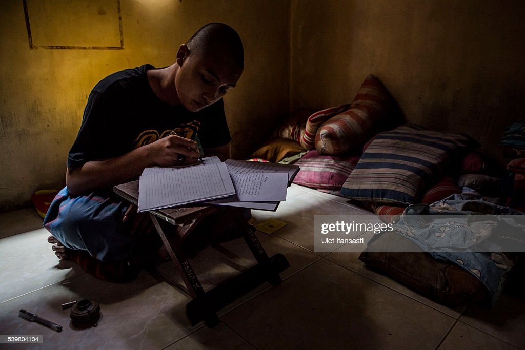 A student writes in Arabic inside his room at the islamic boarding school Lirboyo during the holy month of Ramadan on June 9, 2016 in Kediri, East Java, Indonesia. The Islamic boarding school, Lirboyo, was founded by KH Abdul Karim in 1910, and known to be one of the largest traditional 'Pesantren' in Indonesia, with around 17,000 students in Kediri, East Java. Students at the Pesantren, also known as 'Santri', are separated from their families and spend their days studying Islamic scriptures, reading the Quran and learning Arabic in addition to other activities which begins with the morning prayer at 4am till midnight.