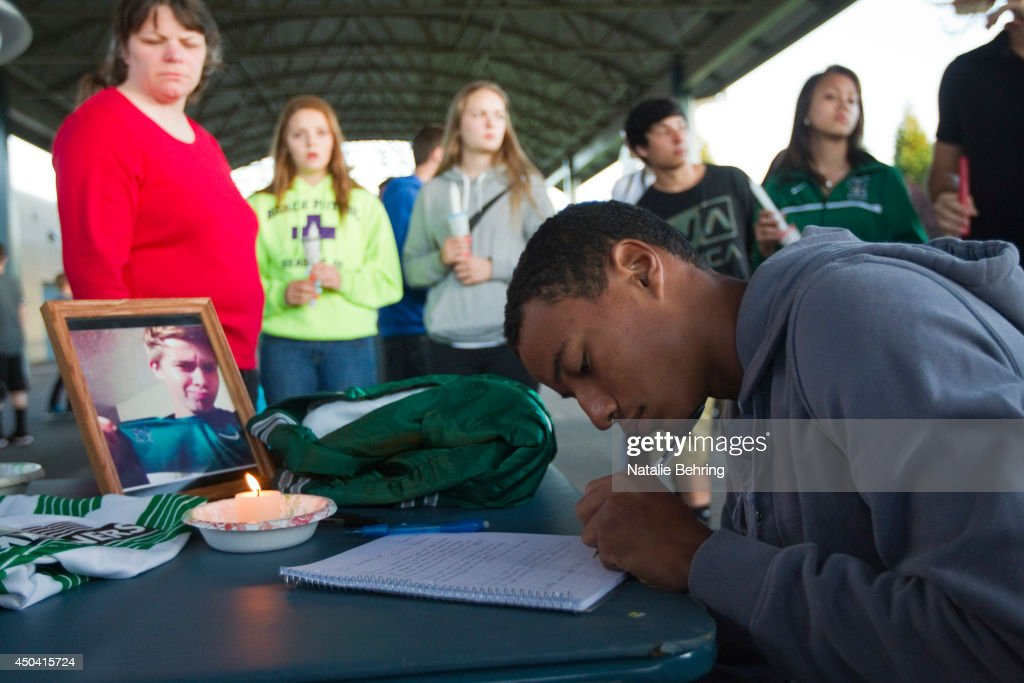 A student writes in as a memorial book Emilio Hoffman the victim of today's school shooting at a candle-light vigil on June 10, 2014 in Troutdale, Oregon. A gunman walked into Reynolds High School with a rifle and shot 14 year old Hoffman to death on Tuesday, in what is the the third outbreak of gun violence in a U.S. school in less than three weeks.