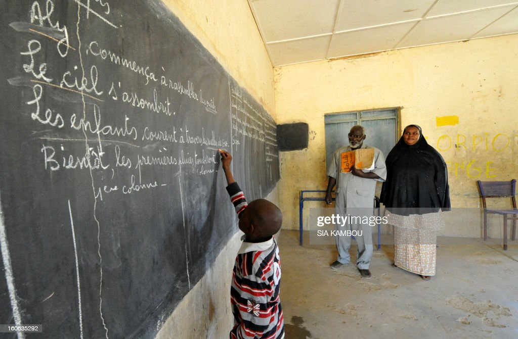 A student writes on a blackboard in a classroom in Gao, in the north of Mali, on the first day of the reopening of schools after the French bombing of Islamist targets, on February 4, 2013. Schools reopened today in Gao after the town was taken on January 26 by French and Malian forces from Islamists who had been occupying it for the last year.