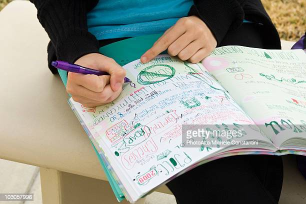 Student writing in notebook illustrated with doodles