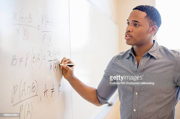 Student writing on whiteboard in class