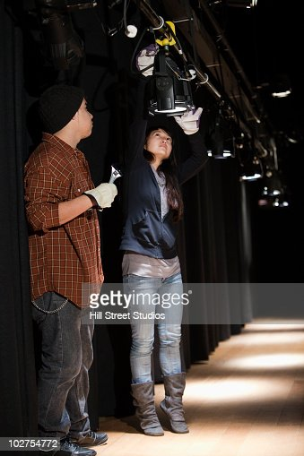Students adjusting lighting backstage at theater