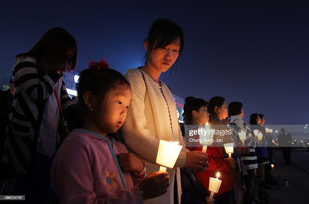 Students and citizens hold candles as they pray for the safe return of missing passengers who were travelling aboard south Korean ferry the Sewol, which sank off the coast of Jindo Island, on April 23, 2014 in Ansan, South Korea. The confirmed death toll is reported to have risen to 150, with more than 150 people still missing.