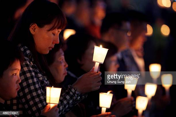 Students and citizens hold candles as they pray for the safe return of missing passengers who were travelling aboard south Korean ferry the Sewol...