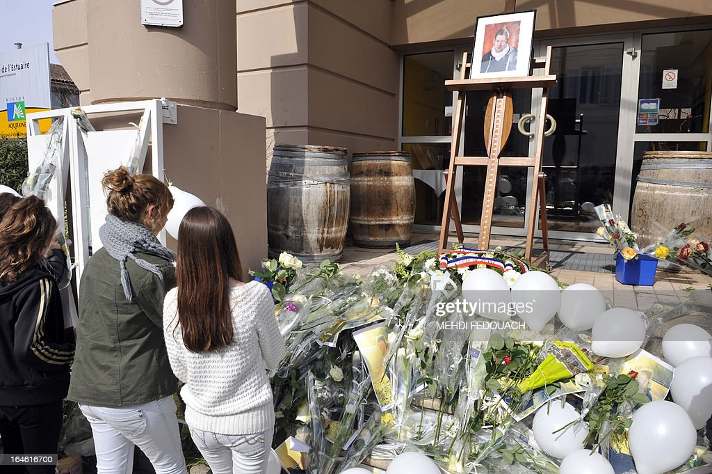 Students and residents lay flowers on March 25, 2013 in front of a portrait of Sylvain, a 15-year-old schoolboy stabbed on March 19 by a 19-year-old comrade in a classroom of the Estuaire college in Blaye, southwestern France.