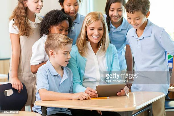 Students and teacher look at homework on a digital tablet