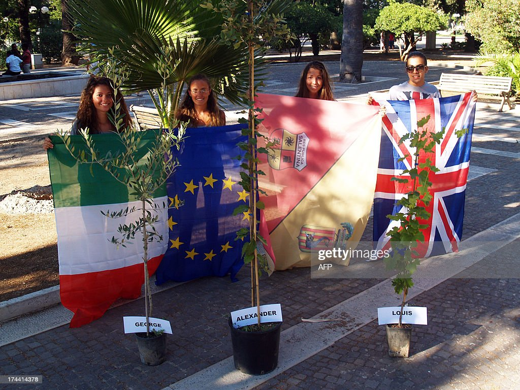 Students and teachers of Galilei Costa High school pose with (from L) Italian, European, Spanish and British national flags in front of three trees before planting them to celebrate the birth of George Alexander Louis, the baby boy of Britain's Prince William and his wife Kate on July 25, 2013 in Lecce.