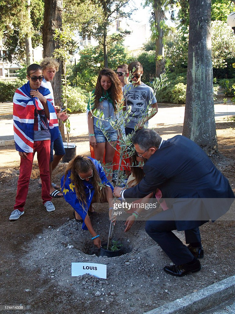 Students and their teacher of Galilei Costa High school plant one of the three trees to celebrate the birth of George Alexander Louis, the baby boy of Britain's Prince William and his wife Kate on July 25, 2013 in Lecce. AFP PHOTO / CONTROLUCE