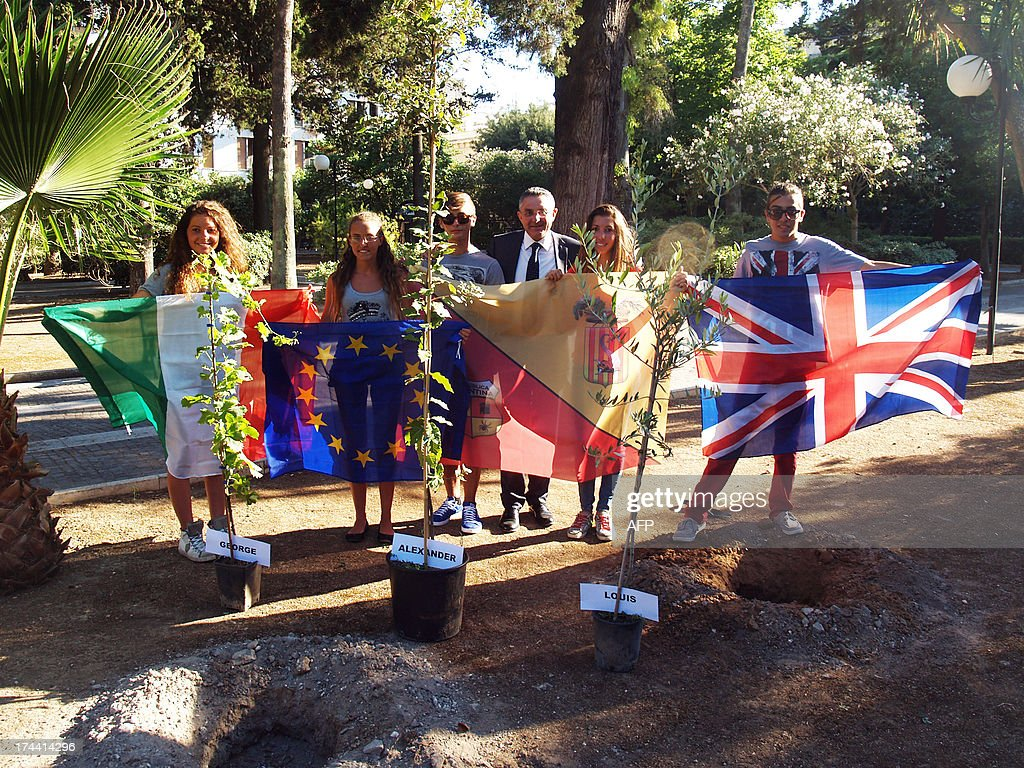 Students and their teacher of Galilei Costa High school pose with (from L) Italian, European, Spanish and British national flags in front of three trees before planting them to celebrate the birth of George Alexander Louis, the baby boy of Britain's Prince William and his wife Kate.