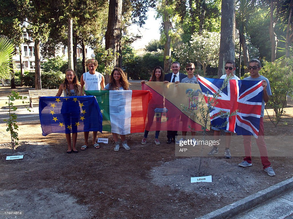 Students and their teacher of Galilei Costa High school pose with (from L) European, Italian, Spanish and British national flags in front of three trees that they have planted to celebrate the birth of George Alexander Louis, the baby boy of Britain's Prince William and his wife Kate.
