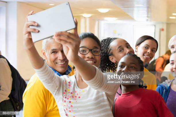 Students and volunteers taking photograph with digital tablet