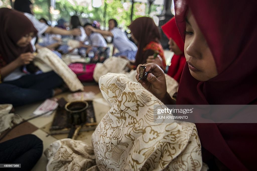 Students apply wax to plain fabric part of the process of making Indonesian batik in the city of Surabaya on eastern Java island on October 2 2015...