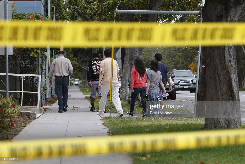 Students are escorted onto Santa Monica College, which remains closed for a second day as investigators gather evidence from crime scenes, to pick up personal belongings they gad to abandon when a gunman on a mass shooting spree entered the campus, on June 8, 2013 in Santa Monica, California. The shootings occurred in various locations about three miles south of a political fundraiser attended by President Barack Obama but Secret Service officials said the two events were not related and that the president was never in any danger. Four people besides the gunman have died from their wounds and five others wounded, including a woman who is close to death.