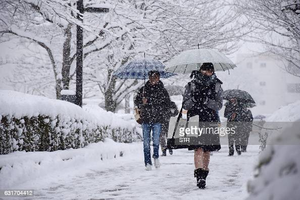 Students are heading to a venue for college entrance examination under snow falling in Gifu on January 15 2017 The Japan Meteorological Agency issued...