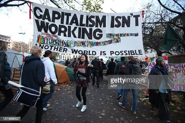 Students arrive at Finsbury Square in London on November 9 2011 under a banner reading 'Capitalism isn't working' for a demonstration against cuts in...