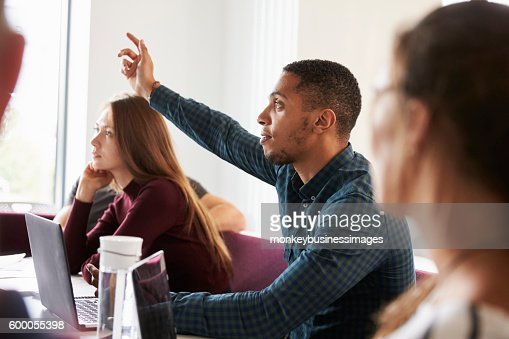 Students Asking Question Whilst Attending Lecture On Campus : Stock Photo