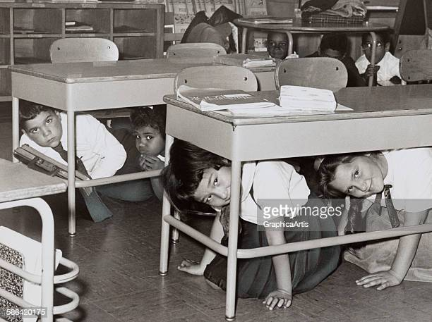 Students at a Brooklyn middle school have a 'duck and cover' practice drill in preparation for a nuclear attack silver print 1962 From the New York...