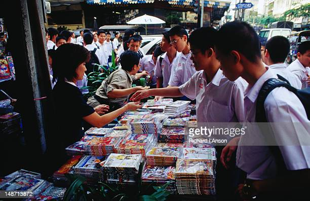 Students at book stall on city street.