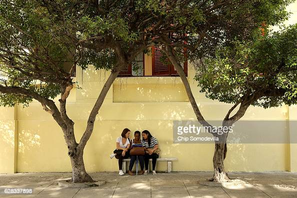 Students at Havana University look at a digital tablet under a spot of shade as daily life resumes in the capital city following a nineday mouring...