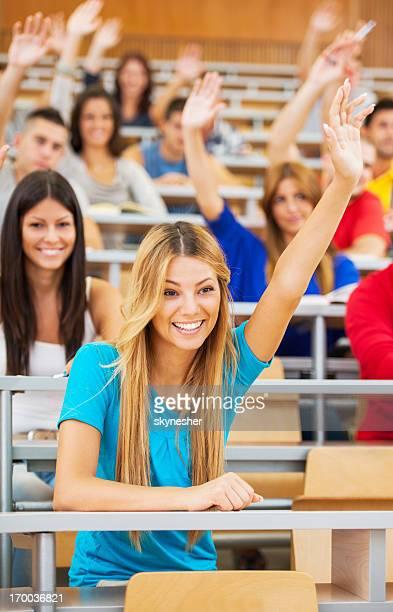 Gli studenti in Aula universitaria alzando le mani.