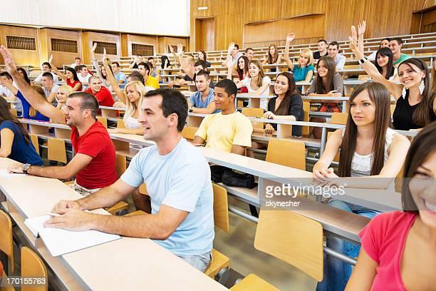 Gli studenti in Aula universitaria alzando le mani per rispondere alla domanda.